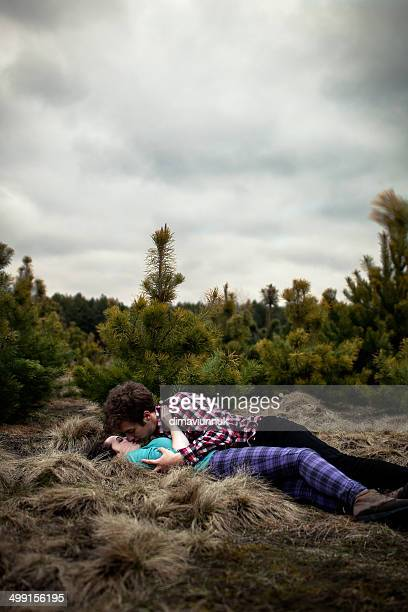 Teenagers (14-15) lying on ground and kissing