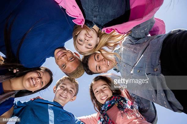 ティーンエイジャー:Multi -ethnic 友人のグループ ハドル 外になります。青い空ます。