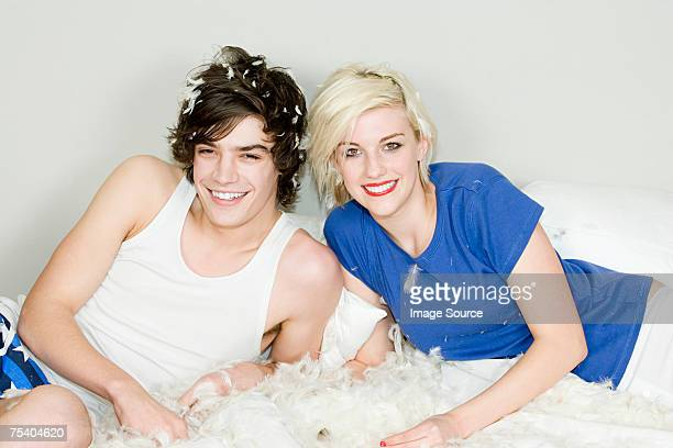 Teenagers on a feather covered bed