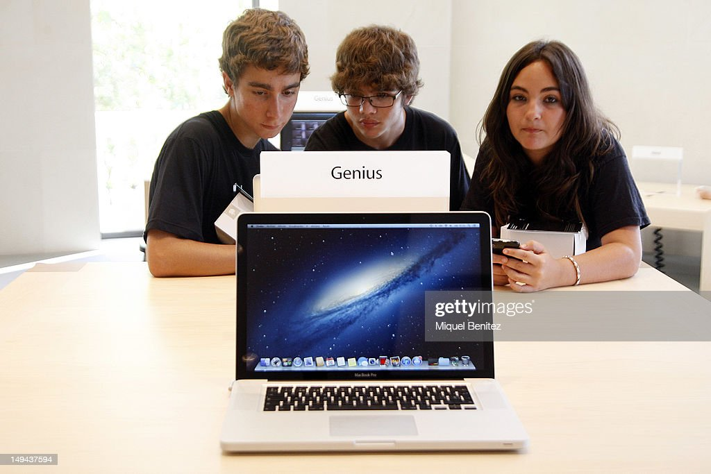 Teenagers play with a MacBook Genius (laptop) on July 28, 2012 in Barcelona, Spain.