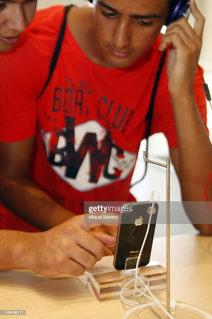 Teenagers play with iPhone (smart phone) and headphones as they attend the opening of Apple's New Barcelona Store in Passeig de Gracia on July 28, 2012 in Barcelona, Spain.