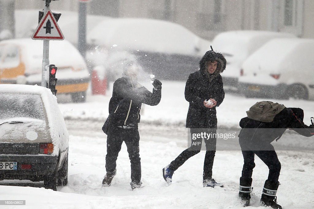 Teenagers play with snow on a snowy sidewalk, on March 12, 2013 in Caen, northwestern France, during a heavy snow storm on France. Overnight Monday nearly 500 cars were blocked near Cherbourg where snowdrifts piled up 60 centimetres (almost two feet) as winds reached 100 kilometres (more than 60 miles) an hour. Twenty-six regions in northwest and northern France were put on orange alert because of heavy snowfalls, which Meteo France said were 'remarkable for the season because of the expected quantity and length of time'.