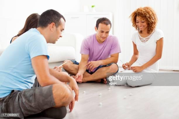 Teenager spielen Brettspiel mit Würfel.