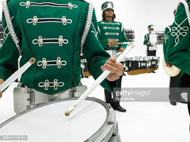 Teenagers (16-18) playing drums in marching band (focus on drum)