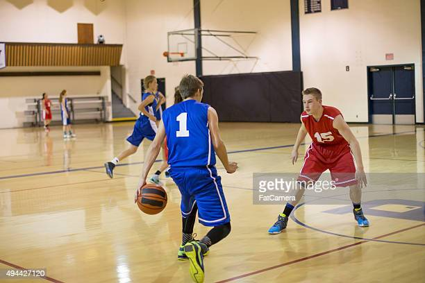 Teenagers playing high school basketball