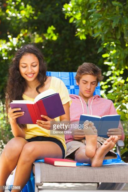 Teenagers reading books outdoors