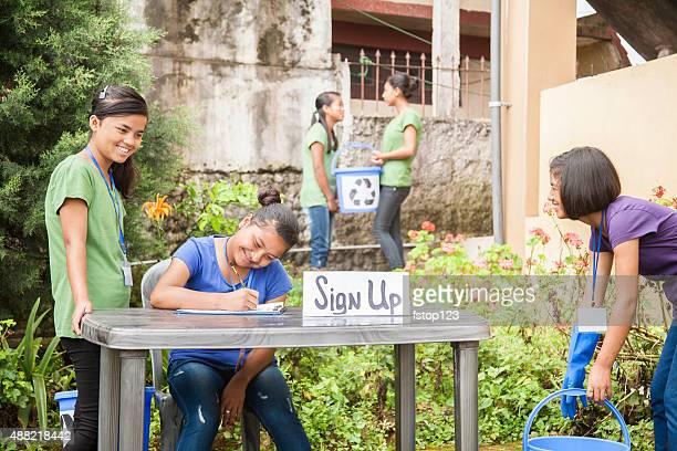 Teenager sich beim recycling Freiwilligen check-in einen Tisch. Multi-ethnische Gruppe.