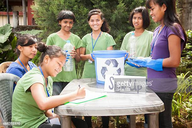 Teenagers register at recycling volunteer check-in table. Multi-ethnic group.