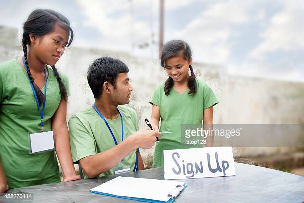 Teenagers register at volunteer check-in table. Multi-ethnic group.
