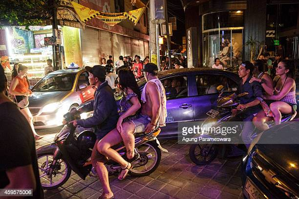 Teenagers ride motorbike taxis on Legian Street during Australian 'schoolies' celebrations on November 26 2014 in Kuta Bali Indonesia This year...