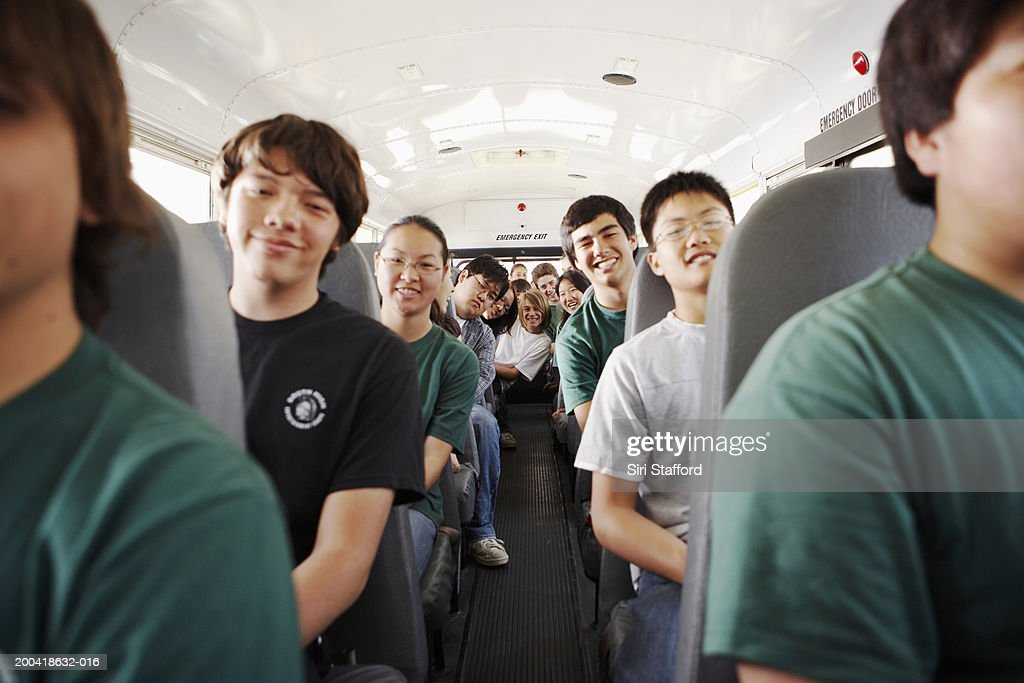 Teenagers (14-18) riding on school bus : Stock Photo