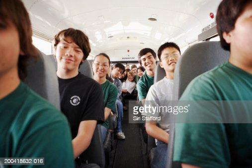 Teenagers (14-18) riding on school bus : Stock Photo