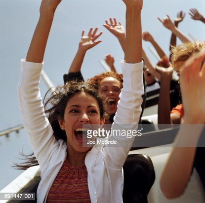 Teenagers (14-17) riding   rollercoaster, hands raised in air