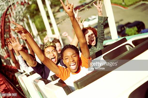 Teenagers (14-17) riding  rollercoaster, hands up in air