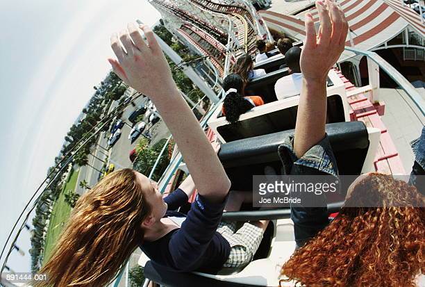 Teenagers (14-18) riding rollercoaster in amusement park