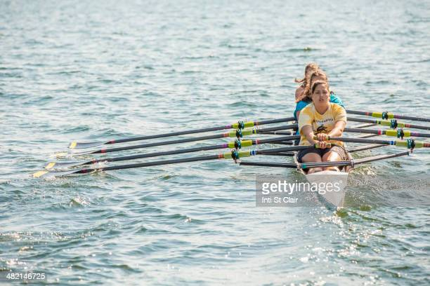 Teenagers rowing together on lake