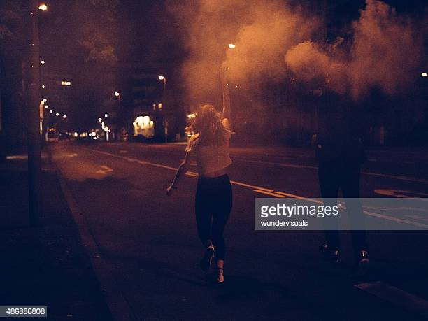 Teenagers running down city street with smoke flares at night