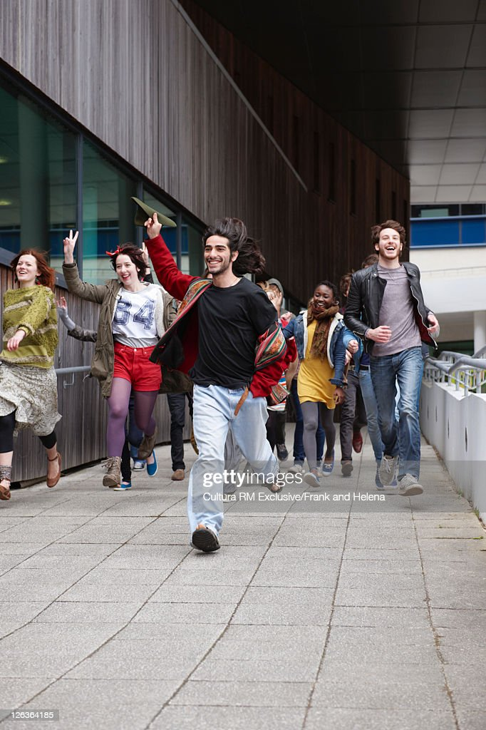 Teenagers running on city street : Stock Photo