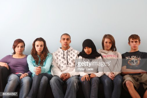 Teenagers sat on sofa : Stock Photo
