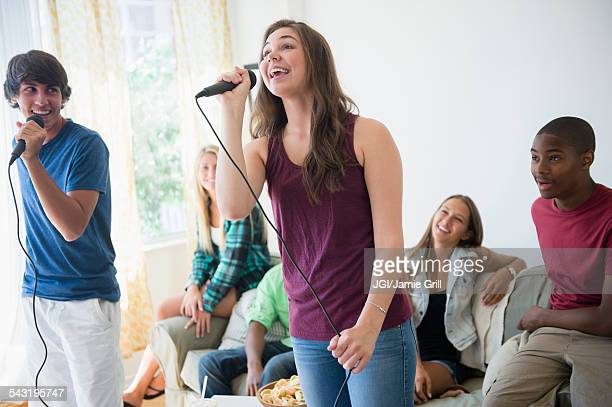 Teenagers singing karaoke at party