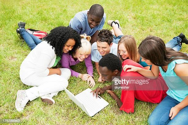 Jugendliche Sitzen im park und mit laptop.