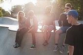 Teenagers sitting on ramp at skate park