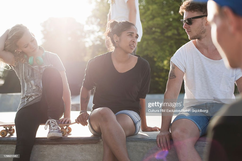 Teenagers sitting on ramp at skate park : Stock Photo