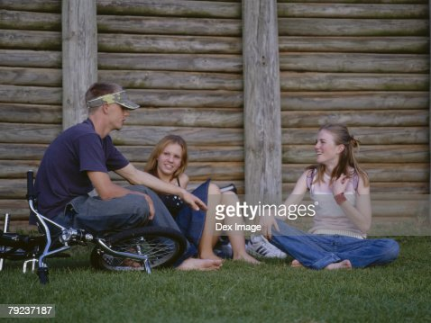 Teenagers sitting together on grass talking : Stock Photo