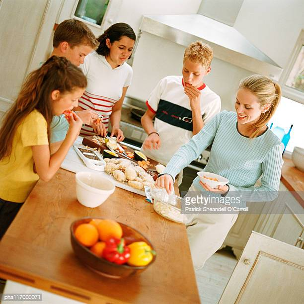 Teenagers snacking around table in kitchen
