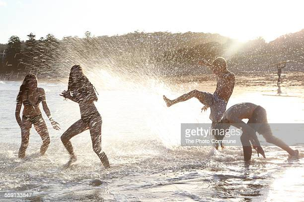 Teenagers splashing on beach sun flare sunset
