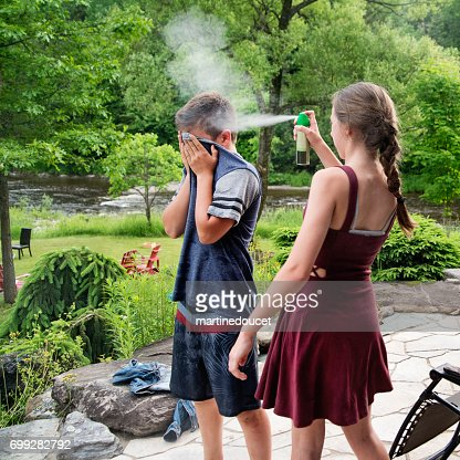 Teenagers spraying insect repellant on each other in summer nature. : Stock Photo