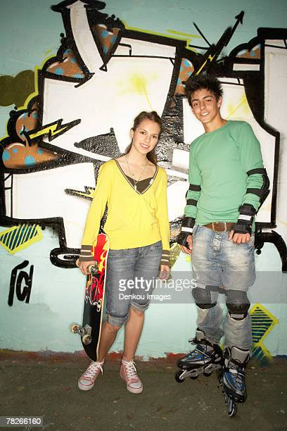 Teenagers standing against a wall.