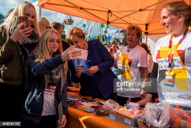 Teenagers take a selfie with German Chancellor Angela Merkel as she signs autographs at a neighbourhood fair organised by the local branch of the...