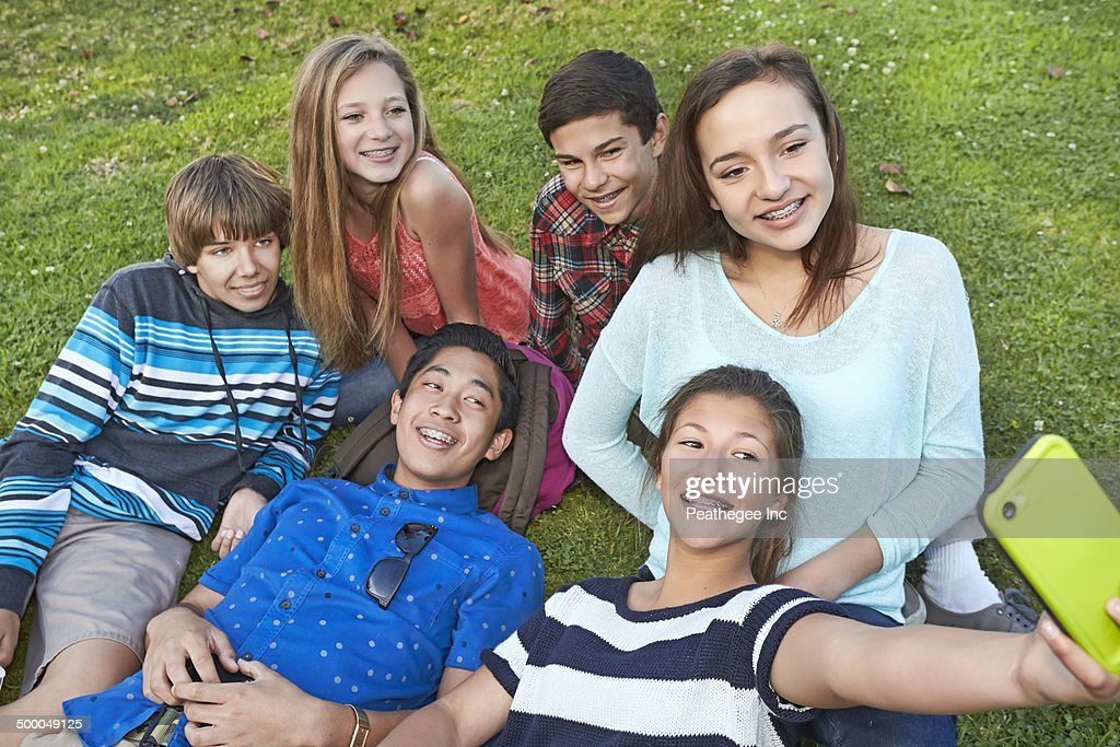 Teenagers taking picture together in grass