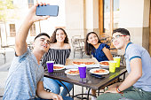 Group of four teenage friends sitting at a cafe table and taking a selfie with a smart phone