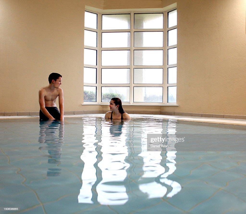 Teenagers talking in swimming pool : Stock Photo