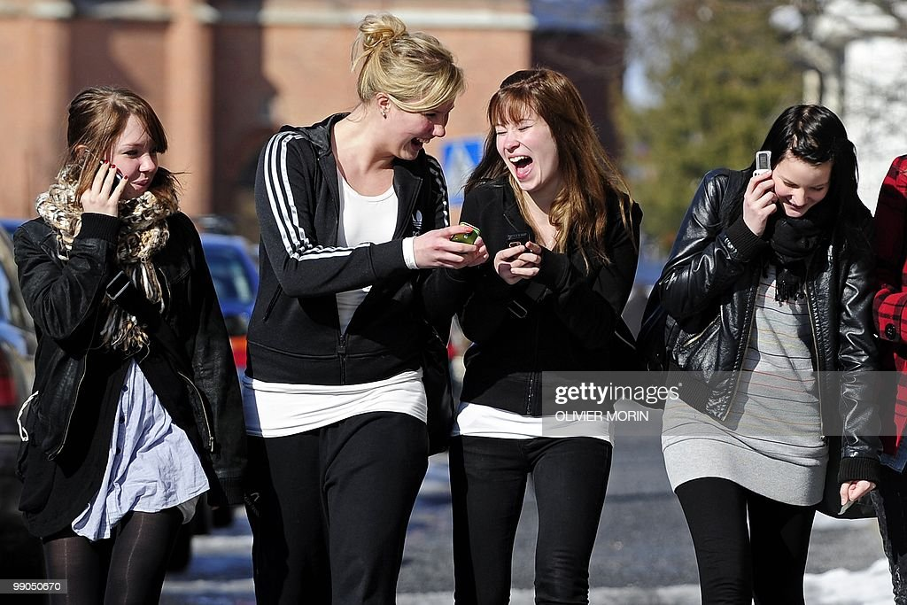 Teenagers use cell phones after school time in Vaasa on March 30, 2010.