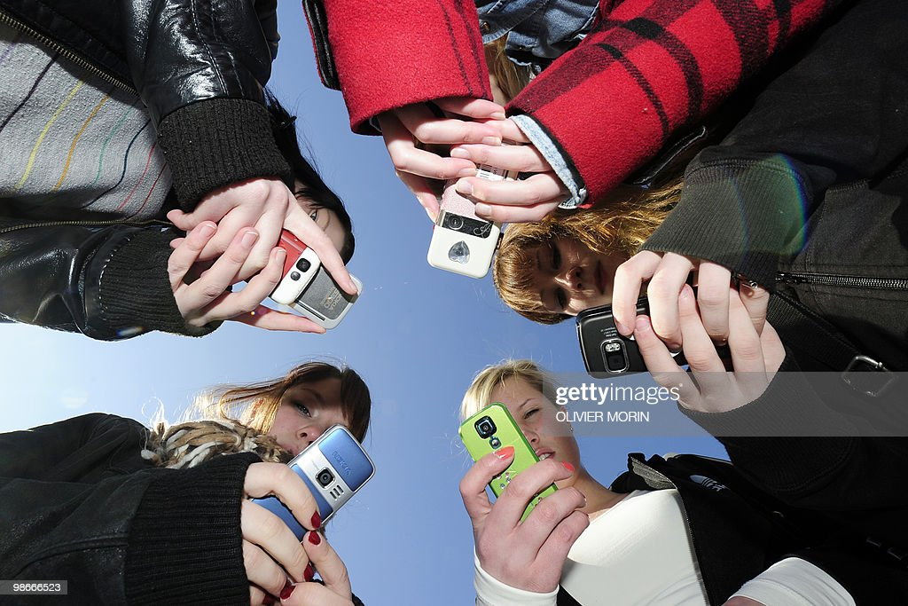 Teenagers use their mobile phones after school time in Vaasa, Finland, on March 30, 2010.