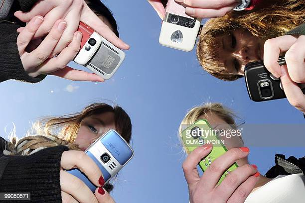 Teenagers use their mobile phones after school time in Vaasa Finland on March 30 2010 AFP PHOTO / OLIVIER MORIN