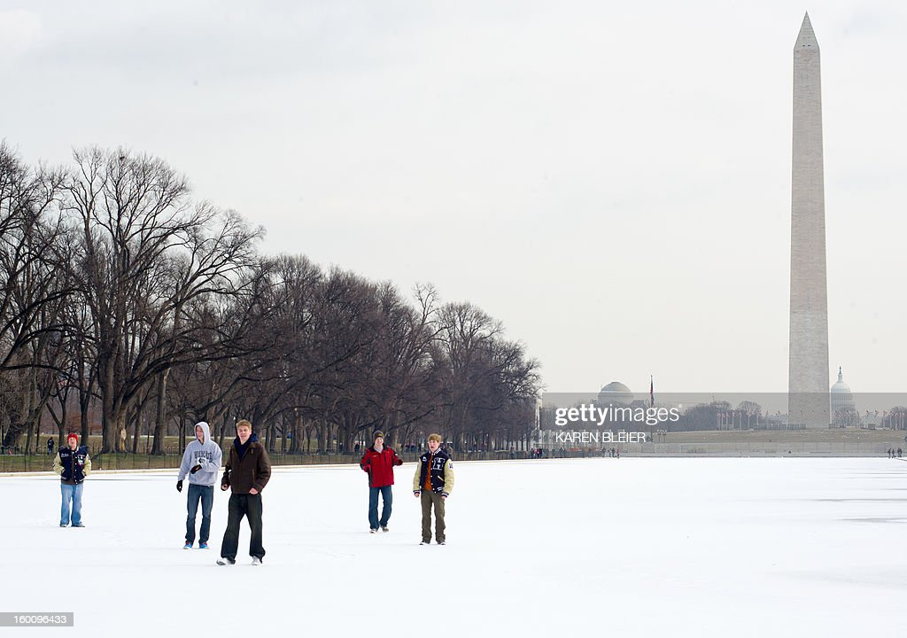 Teenagers walk on the ice on the reflecting pool near the Washington Monument January 26, 2013 in Washington, DC. Below freezing temperatures on the East coast over the past few days have caused some areas of the lengthy pool to freeze over. AFP PHOTO/Karen BLEIER