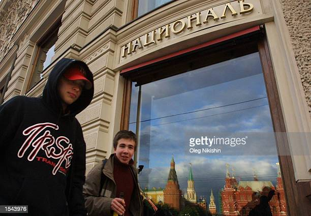 Teenagers walk past the National hotel as the Kremlin is seen in the window reflection May 2002 in Moscow Russia US President George W Bush is...