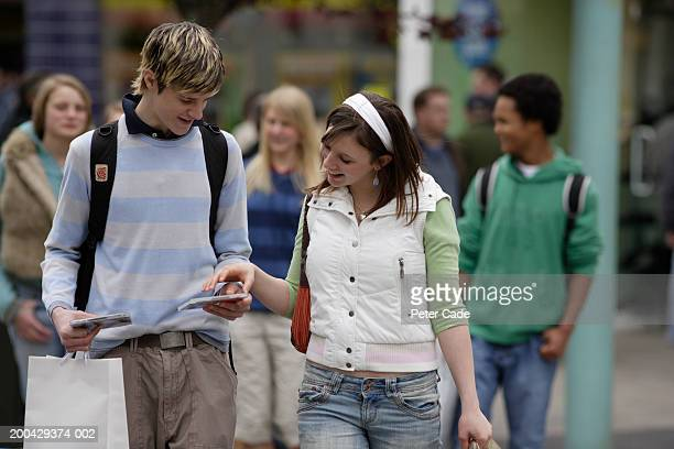 Teenagers (16-18) walking on street, boy showing girl cds