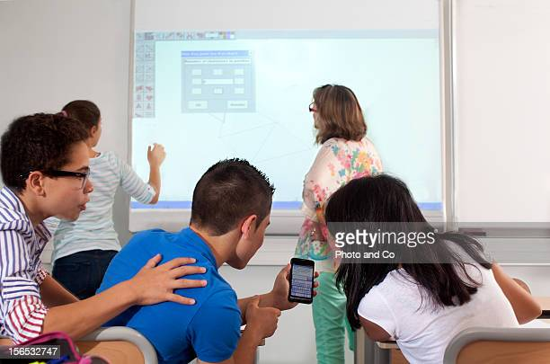 teeneger in classroom with a mobil phone
