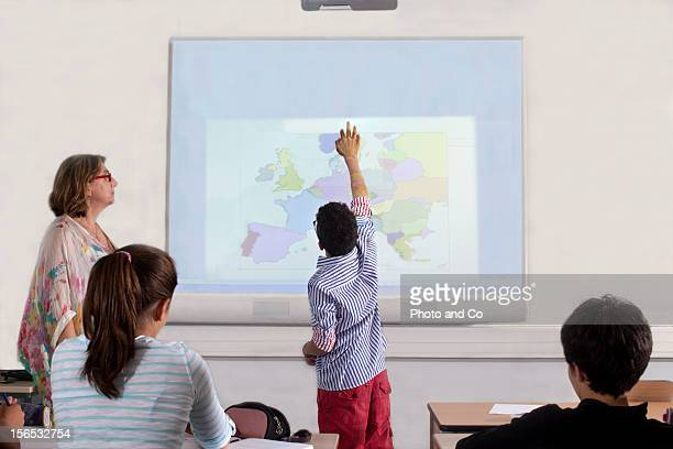 teeneger in classroom with interactive white board