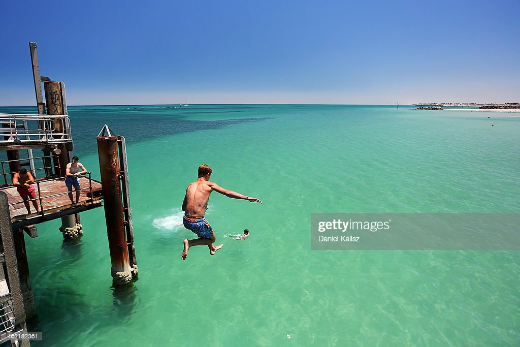 A teengager jumps off the Glenelg jetty during a heat wave at Glenelg Beach on January 13, 2014 in Adelaide, Australia. Temperatures are expected to be over 40 degrees celsius all week with health authorities warning the young and elderly to remain indoors.