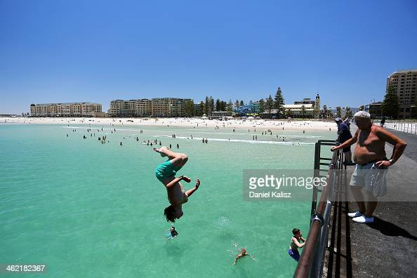A teengager jumps off the Glenelg jetty during a heat wave at Glenelg Beach on January 13 2014 in Adelaide Australia Temperatures are expected to be...