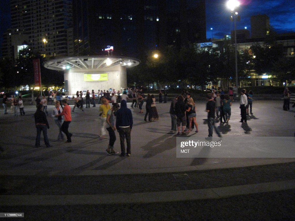 Teens and older adults dance to swing music in Rosa Parks Circle in Grand Rapids Michigan An ice rink in winter the circle is home to outdoor music...