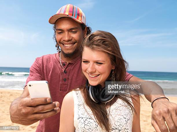 Teens at beach with smartphone