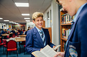 Two teenage students are standing together in the school library, talking and reading books.