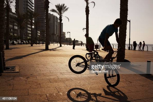 Teens do stunts on their bicycles along the corniche at the start of the summer season for the Mediterranean city on June 23 2014 in downtown Beirut...